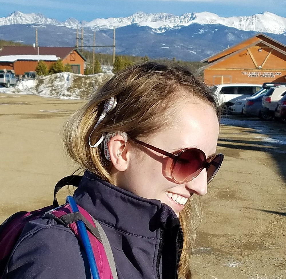 Shannon is front and center, smiling and wearing sunglasses. Her cochlear implant is white and on her left ear. She is happy because she is in Colorado. Her blonde hair is down and she is dressed for snowshoeing in a black jacket. The rocky mountains are blue and snow covered in the background.