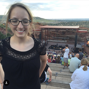 Shannon is wearing a black shirt and glasses. The Red Rocks Amphitheater is in the background. She is closing her eyes and smiling.