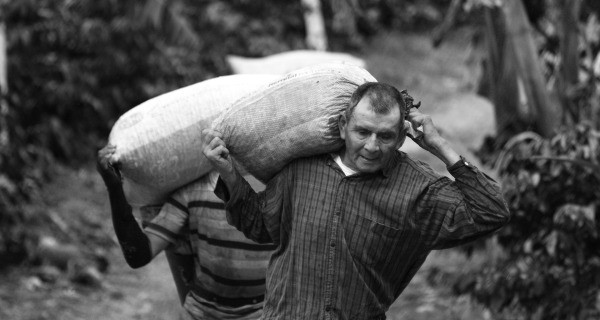 Man working hard while carrying a large bag of goods.