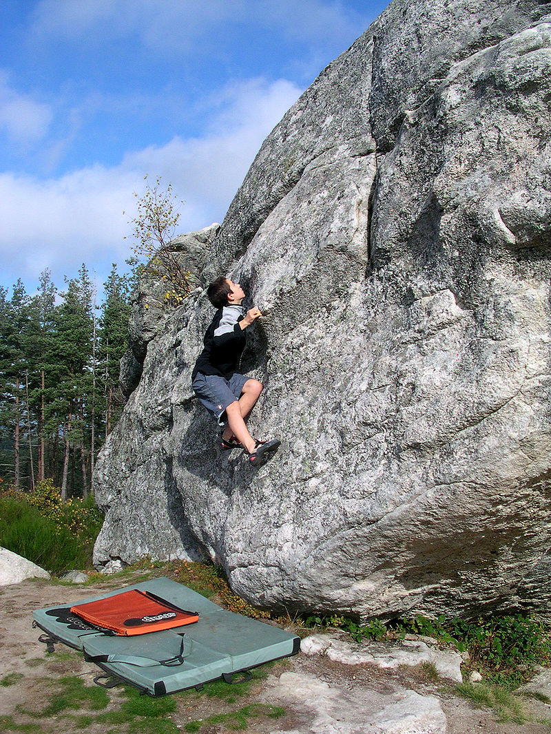 Boulderer mit Crashpad in Saint Just im Département Cantal, Frankreich