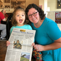 Amanda's daughter Violet showing off her mom's front page Farmers' Weekly Review