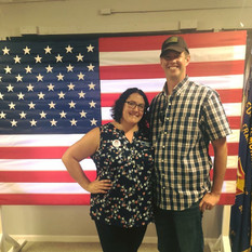 Amanda and her husband Dan in front of the flag from their wedding they donated to their VFW post, July 2018