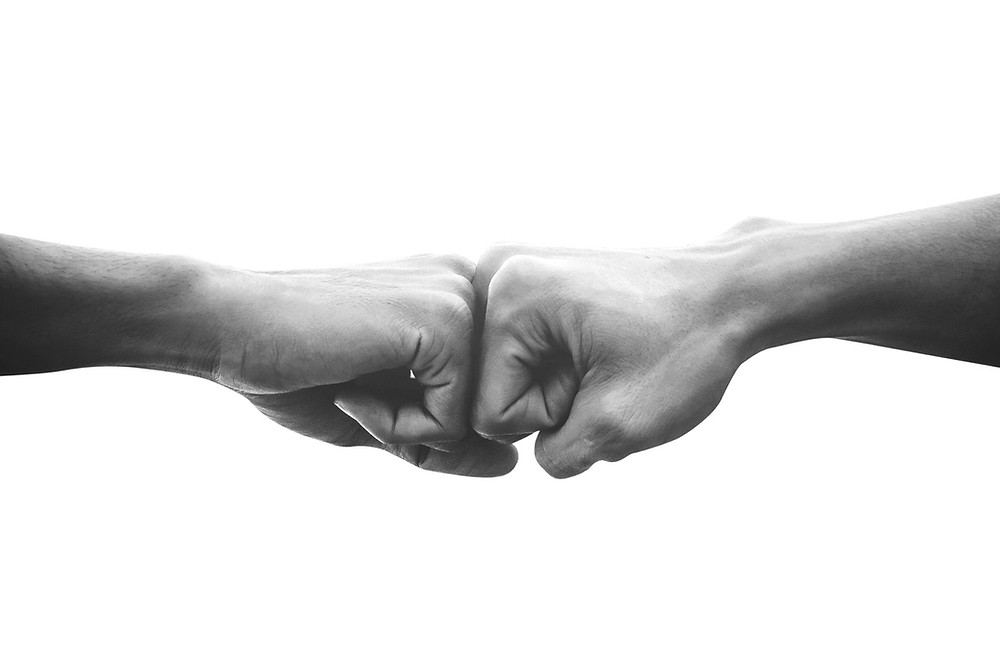 Two fists bumping to show how to bulletproof your partnership