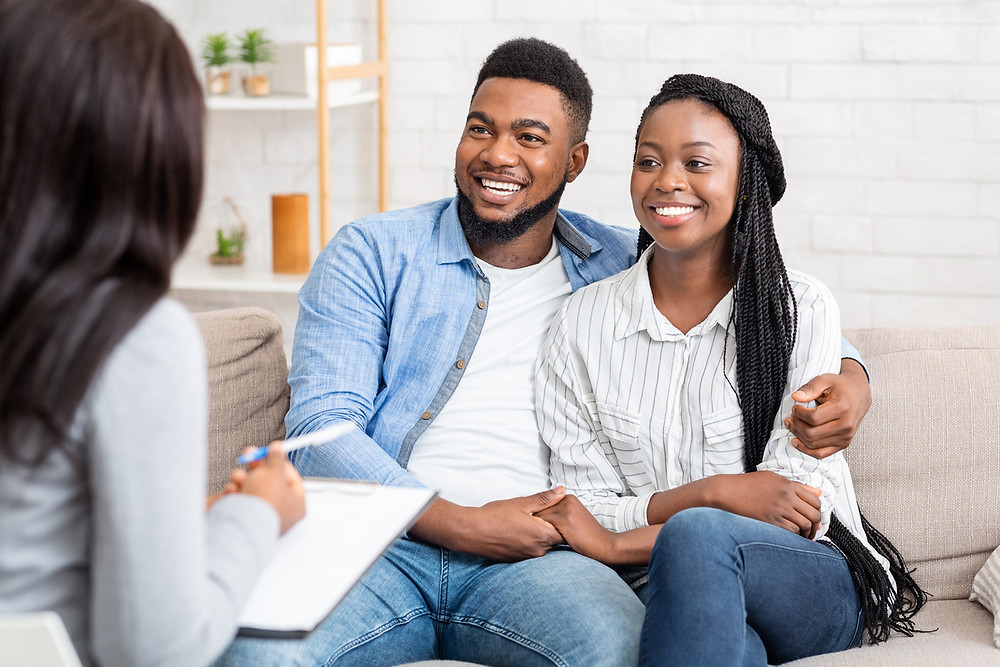 A couple sits smiling on a couch holding hands while improving their communication technique at couples therapy to help their relationship grow