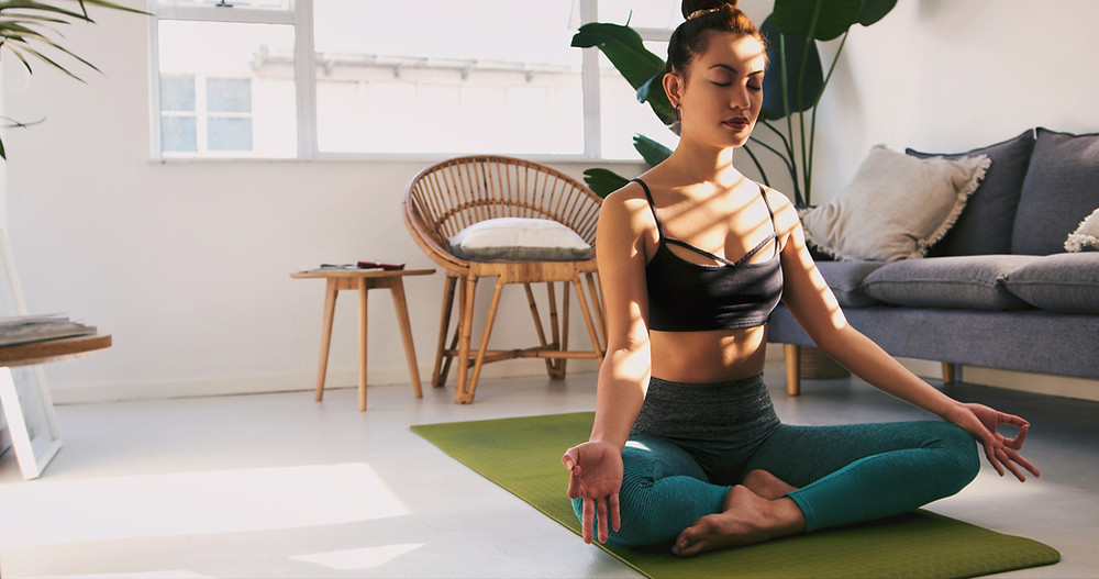 A woman practices yoga with her eyes closed and sitting on a mat to strengthen her mind-body connection