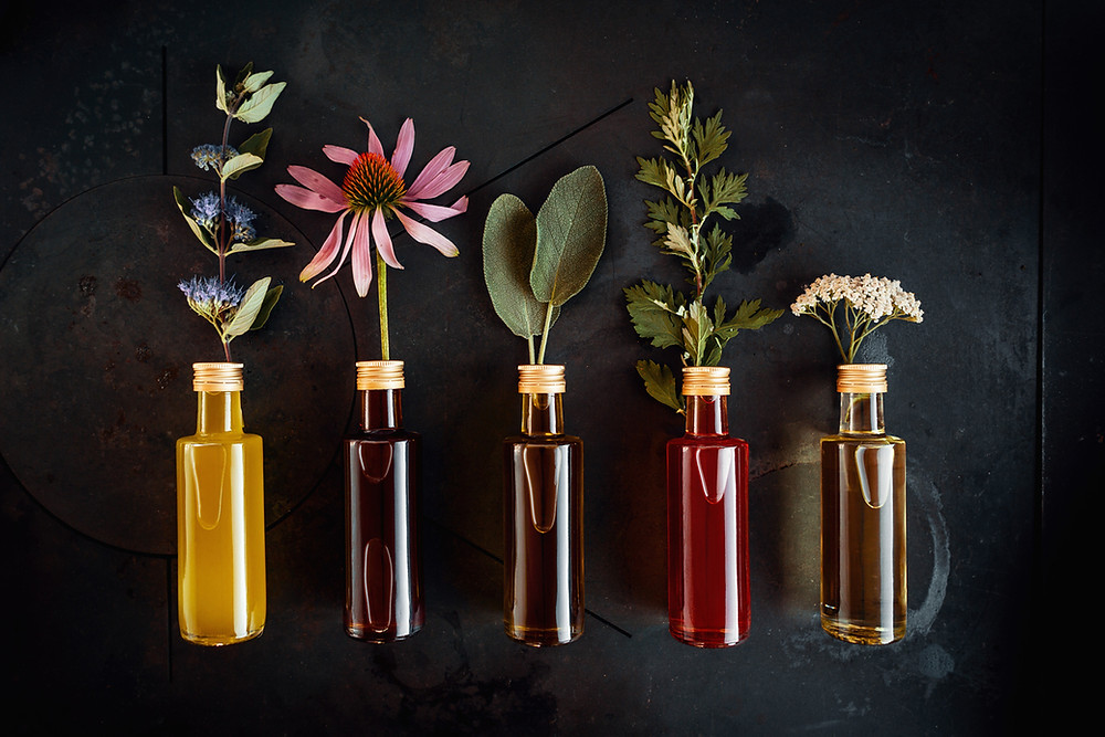 Vials of essential oils with flowers sticking out used for aromatherapy