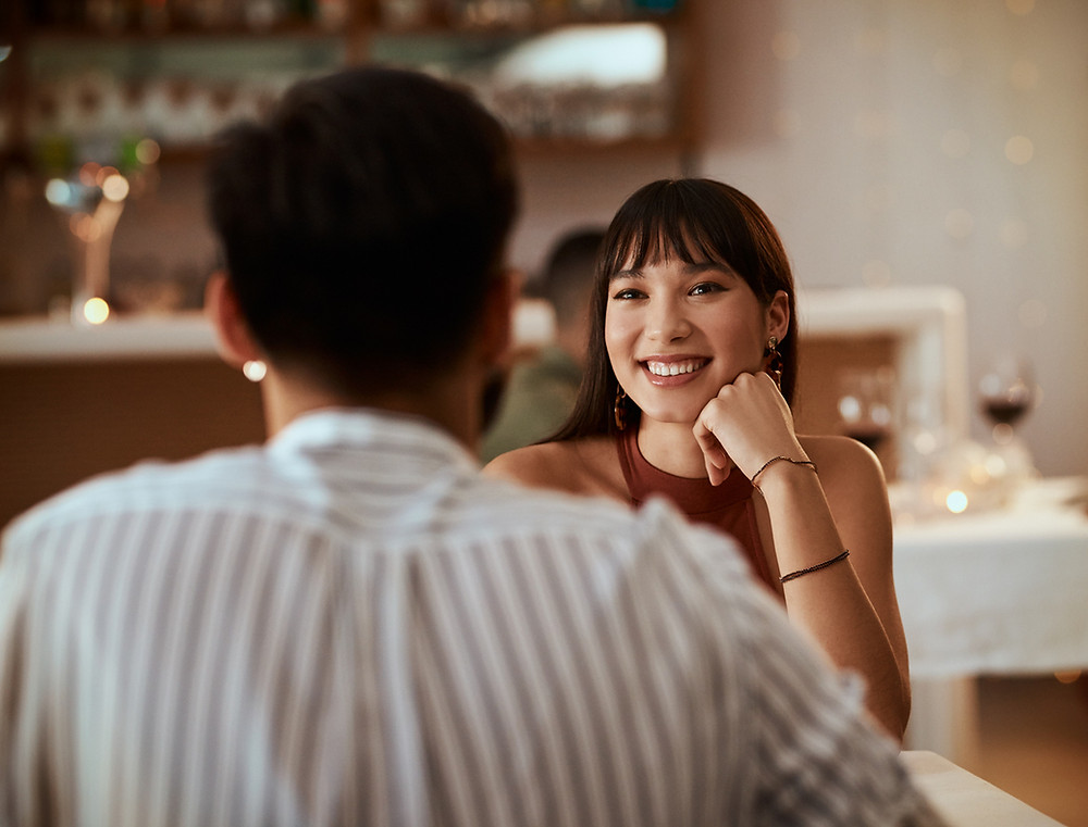 A woman smiles at her dinner companion but looks for red flags while dating him