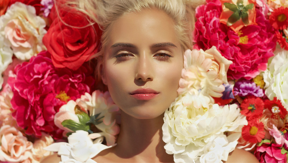 woman's glowing face surrounded by blooming flowers