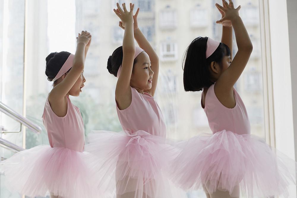 three girls posing in pink tutus