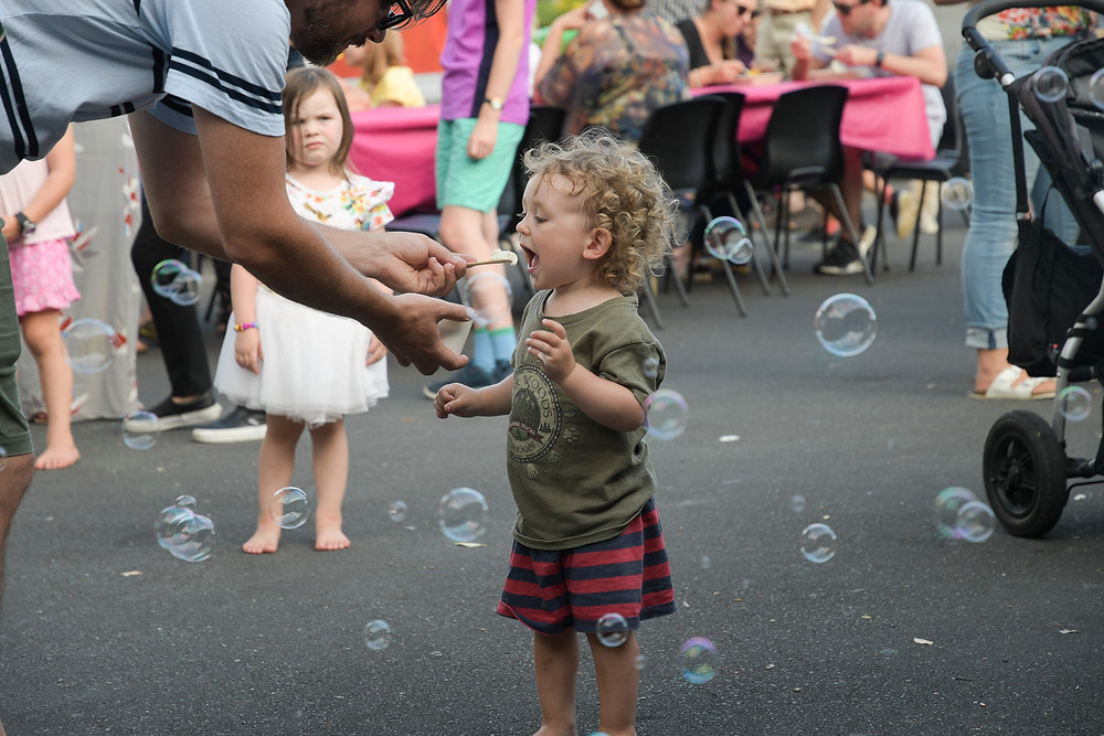 Children playing with bubbles and eating gelato at Green Bay Street Food