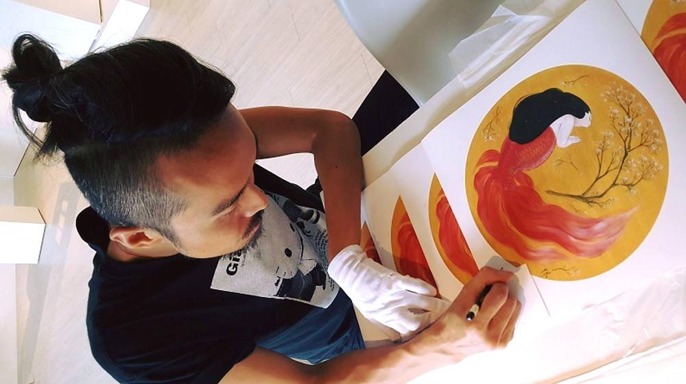 藝術家專注地為限量版畫親簽版數與姓名