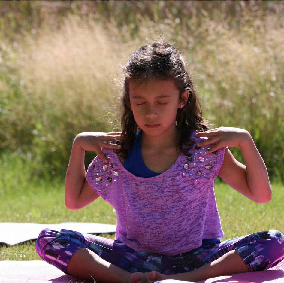 Young girl meditating in field of grass