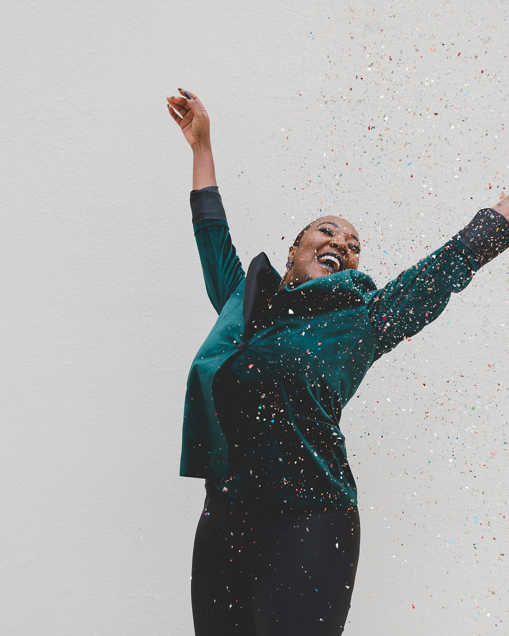 A Black woman in a turquoise velvet jacket jumping with delight.