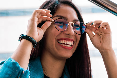 A smiling woman trying on eye glasses.