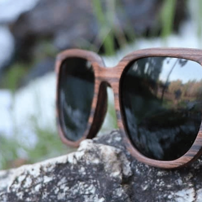 A pair of wood Upland eye glasses on a rock with green in the background.