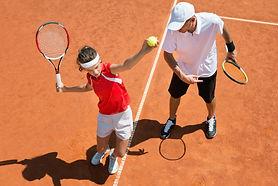 Junior tennis player practicing service