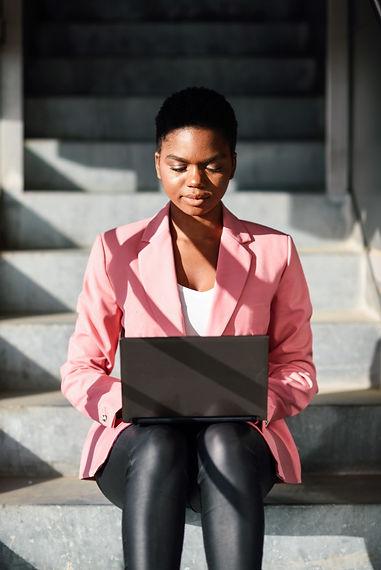 black-woman-sitting-urban-steps-working-