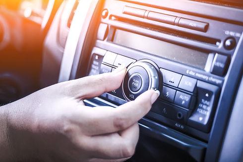woman turning button of radio in car_edi