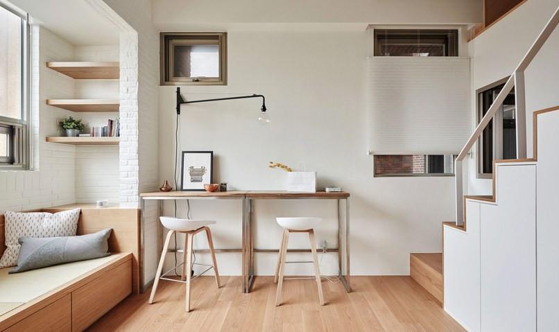 Sofá com gavetões, estantes apoiadas na viga e bancadas de trabalho com banquetas baixas dão leveza e versatilidade ao ambiente.
