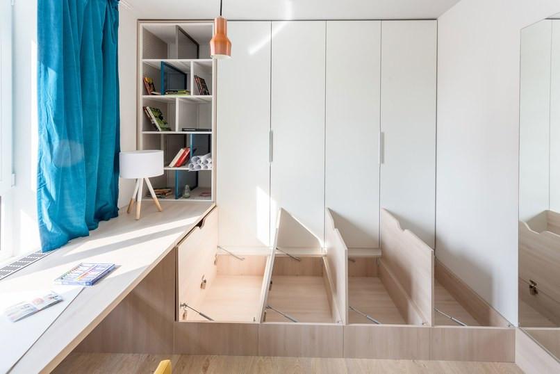 Compartimentos estilo bau sob a cama, compondo a marcenaria planejada deste quarto.