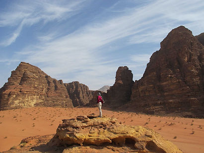"""Described by T.E. Lawrence as """"vast, echoing and God-like..."""", it is at Wadi Rum that red sandstone rocks reach up from the desert floor to the high desert sky.  The area is at its most dramatic early and late in the day, when the soft light and blue sky create a coppery effect on the sand.  Here you hike through canyons and wadis, camping like the local Bedouin among the rock formations.  Imagining ancient caravans of spice traders travelling far and wide to sell their wares, you walk into Petra, the Rose Red City hewn from the rock.  Here you discover tombs, temples and treasuries, and as you climb up to find magnificent views and vistas, you begin to understand why Lawrence loved this land."""