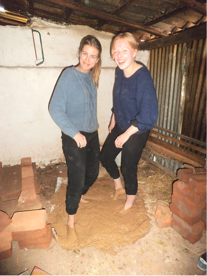 voluntarios usando los pies para mezclar la tierra y el agua_edited