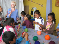 Cicely teaching knitting  to the children