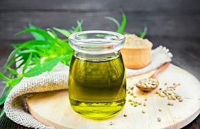 Hemp oil in a glass jar, grain in a spoo