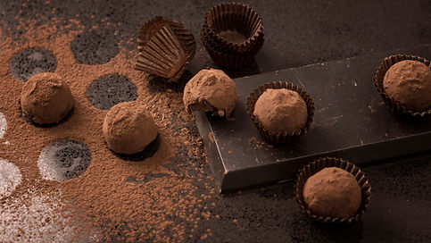 Traditional chocolate truffles dusted with cocoa powder and a bar of chocolate.