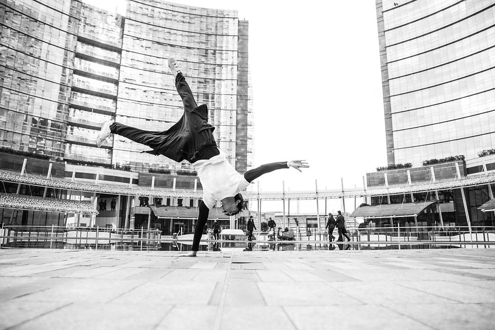 Urban dancer or freerunner doing acrobatic trick upside down in a plaza between skyscrapers.