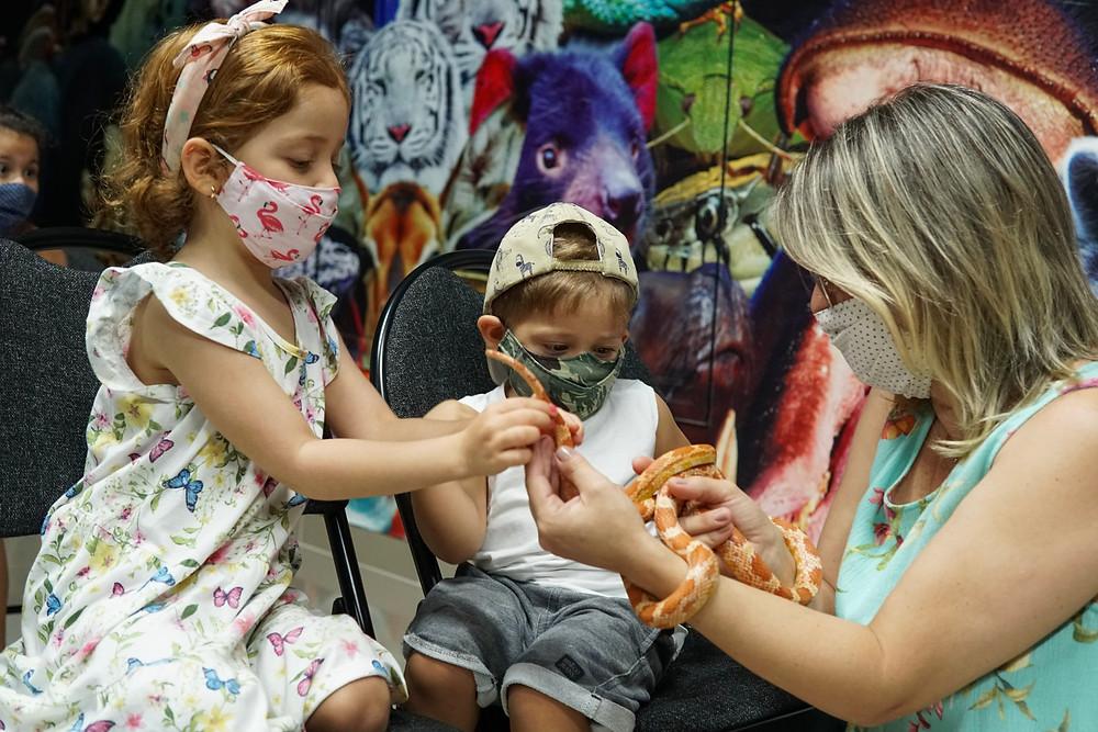 Crianças interagem com cobra durante aula de educação ambitenal do projeto selva viva