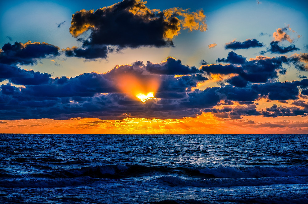 Sunset forming a silhouette of a heart in the clouds over the ocean