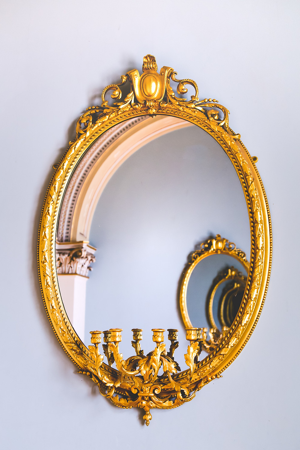 Golden mirror on a wall reflecting another golden mirror into infinity