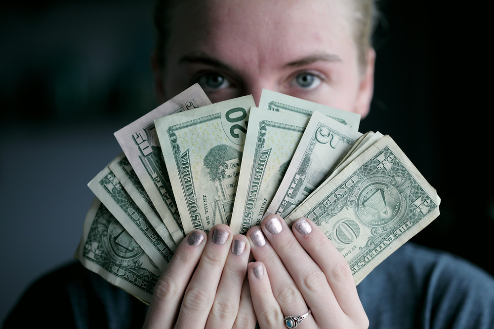 Person holding American currency fanned out in front of their face
