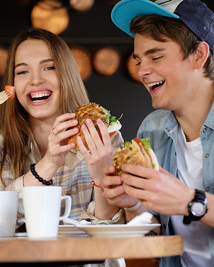 Cheerful multiracial friends eating in a