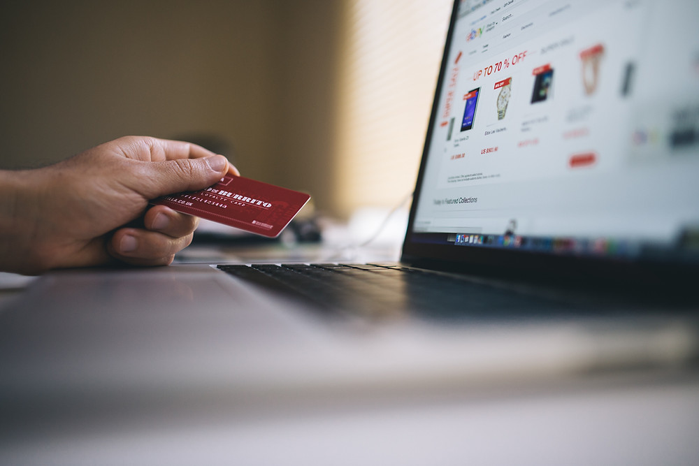 Hand holding a red loyalty gift card while looking at an online sale on laptop.