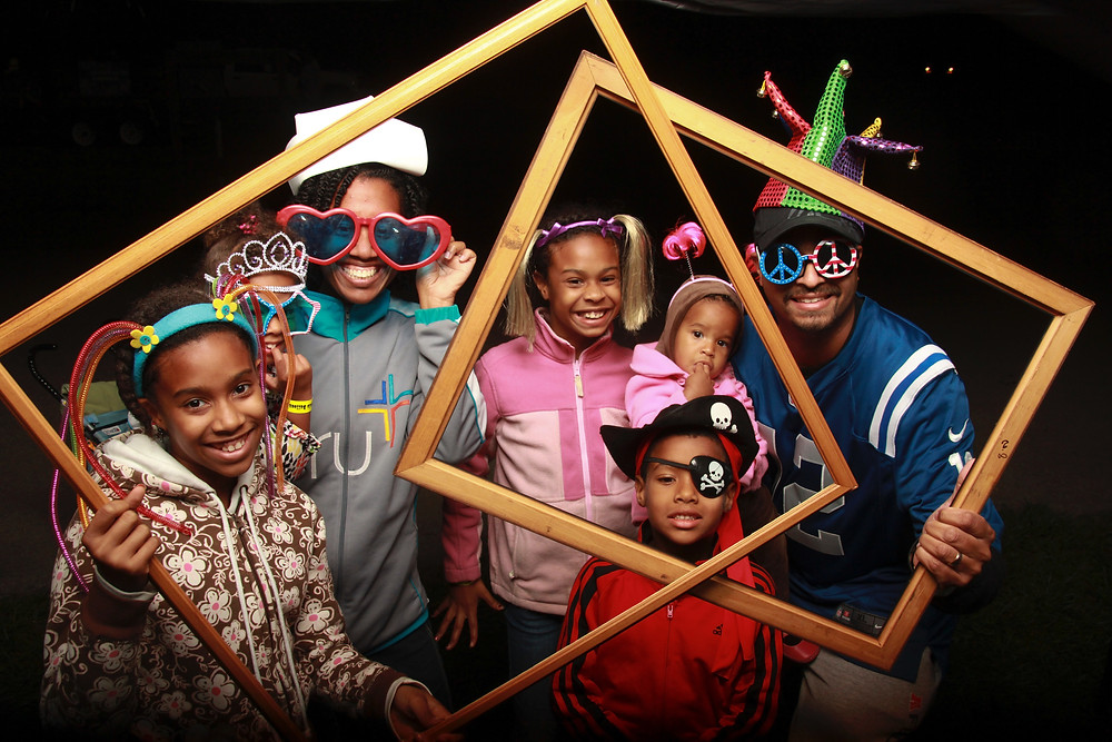 family holding large prop frames and wearing fun headbands and sunglasses for photo booth picture.