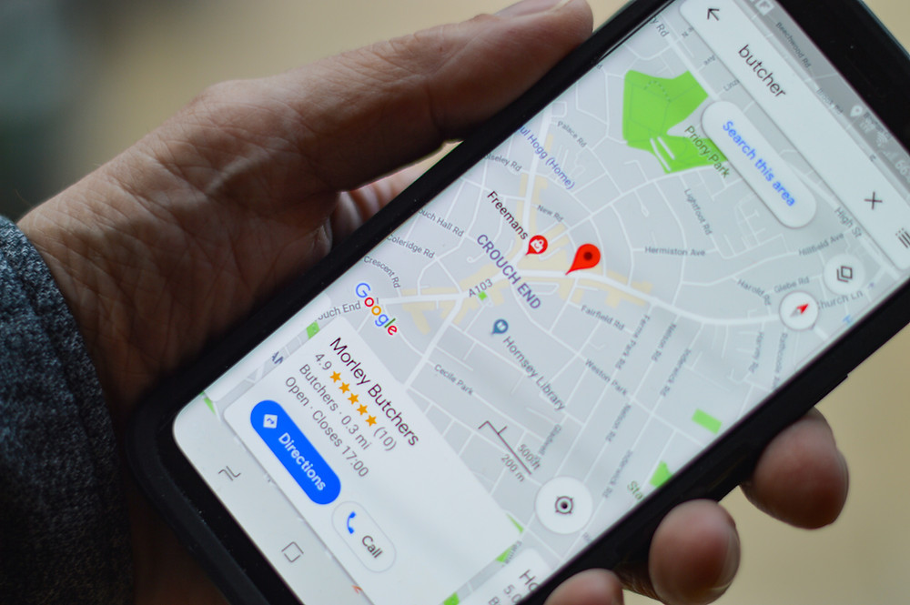A mans hand holding a smartphone with Google Maps  looking at a local business listing.