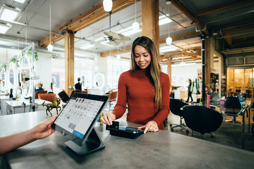woman pays by credit card on POS system at a San Diego salon.