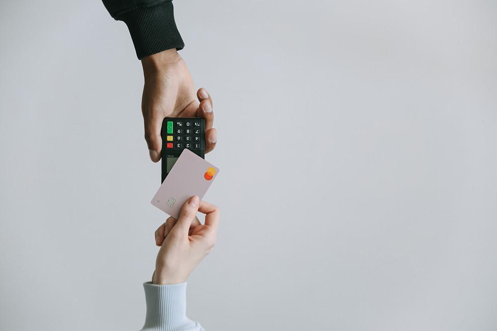 Image of man hand holding credit card reader and woman hand holding credit card.