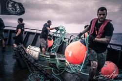 150207-SA-147-BB-deck-crew-retrieve-bouys-after-Thunder-starts-setting-net