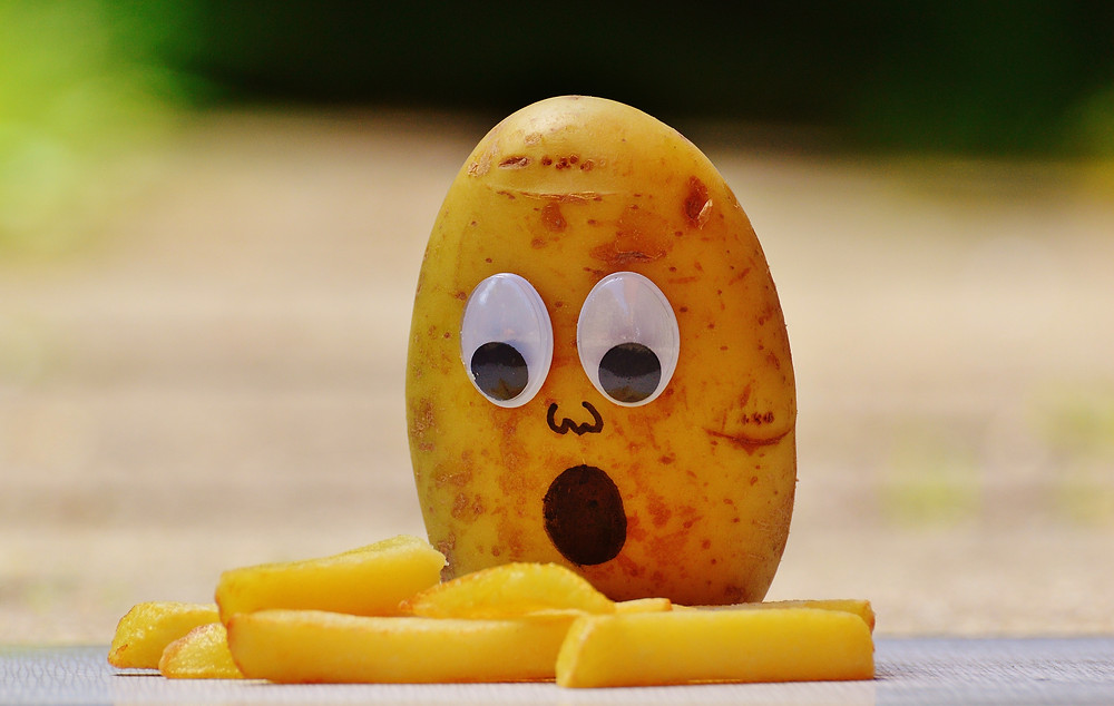 Potato with googly eyes staring at some french fries in shock