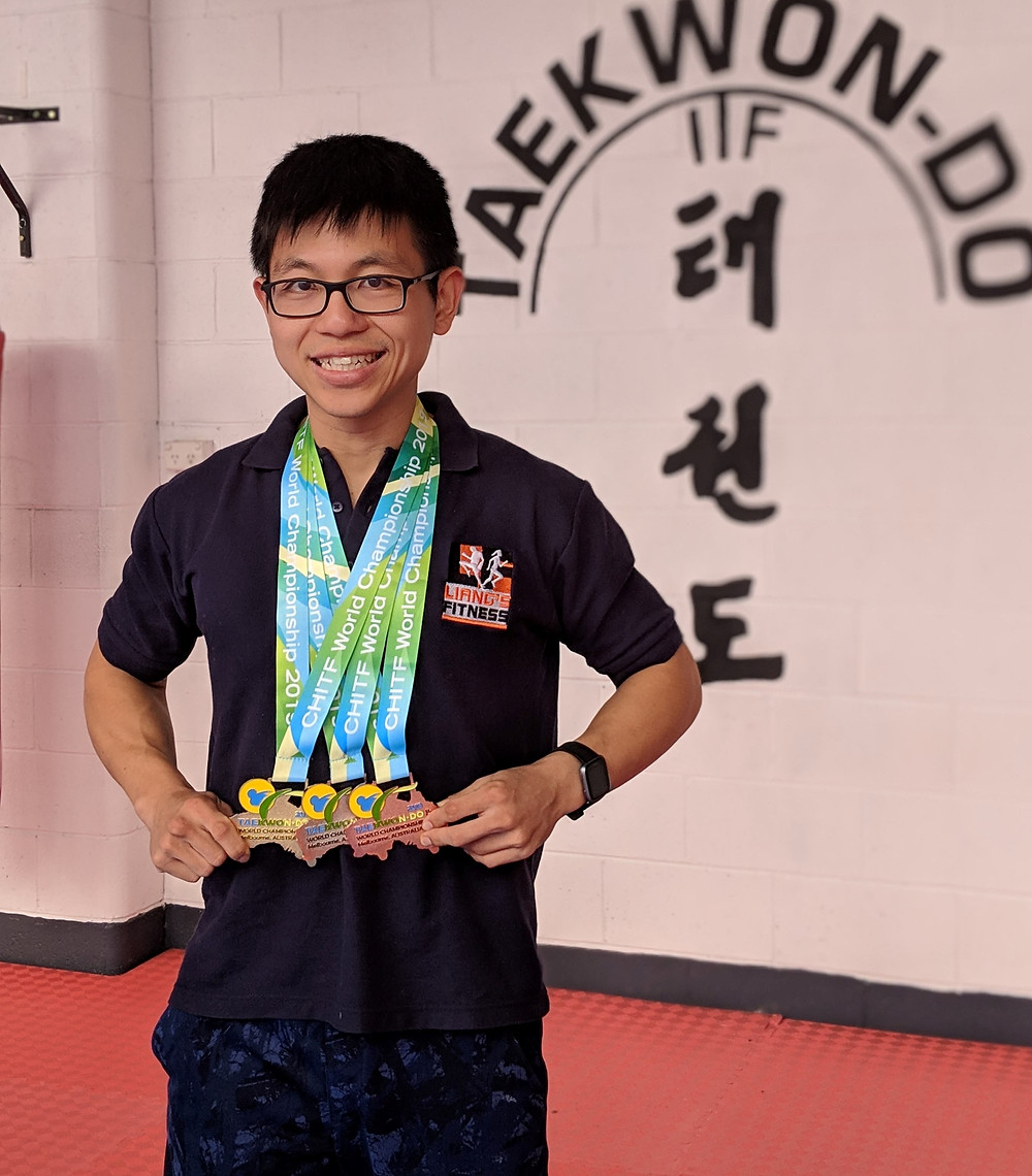 Liang wearing 3 Taekwon-Do medals around his neck.