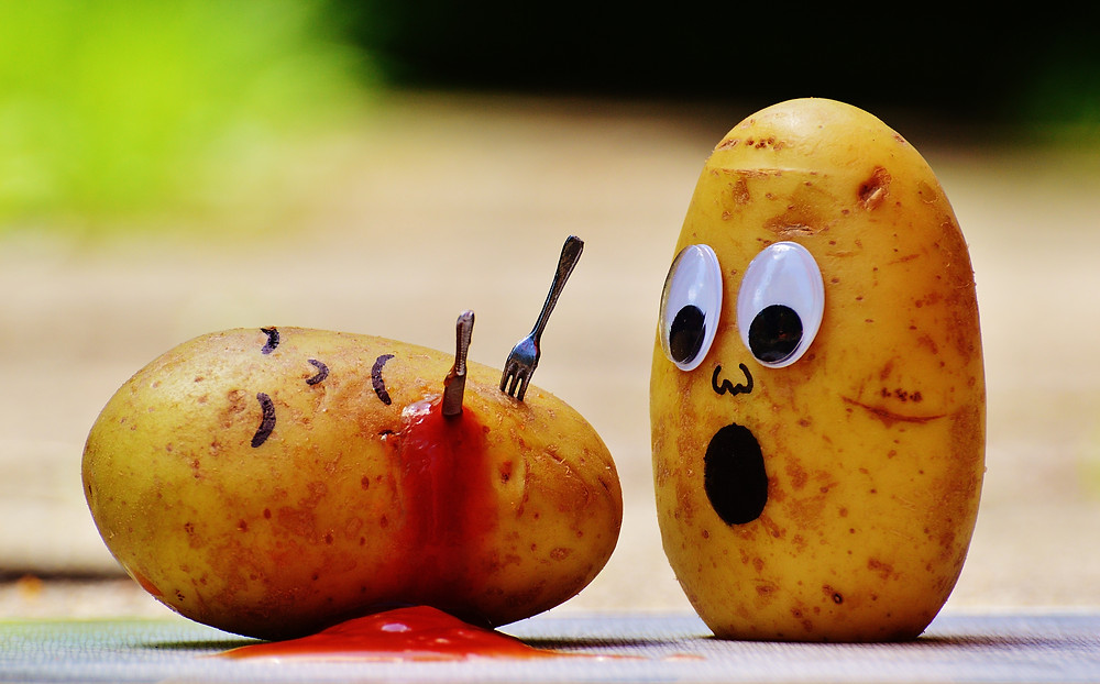 A picture of two potatoes with faces drawn on. The one on the left has a fork and knife stuck in it and ketchup dripping down it like blood. The one on the right is staring at the other one in shock.