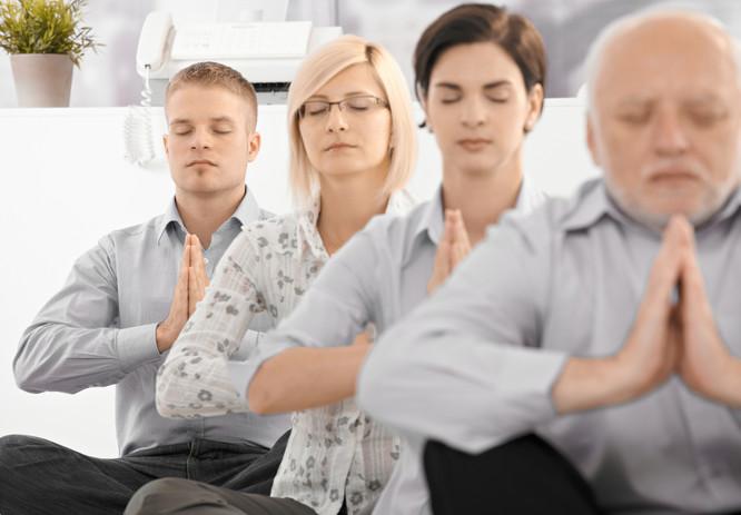 Businessteam doing yoga exercise in offi