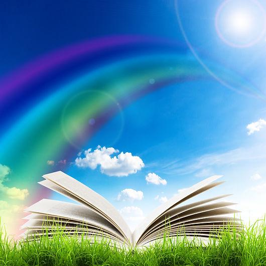 Open book in green grass over blue sky.jpg