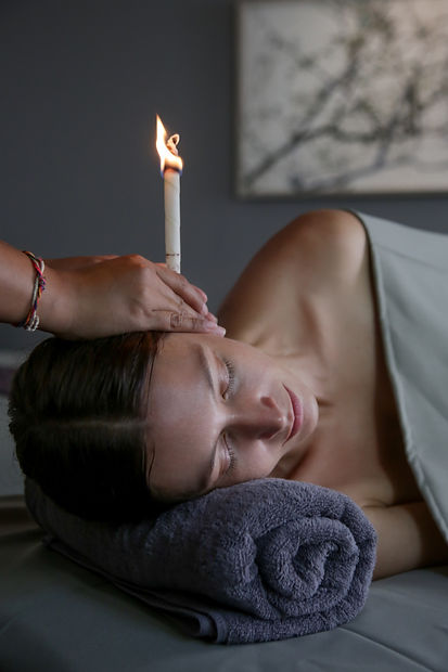 Woman receiving ear candle treatment at