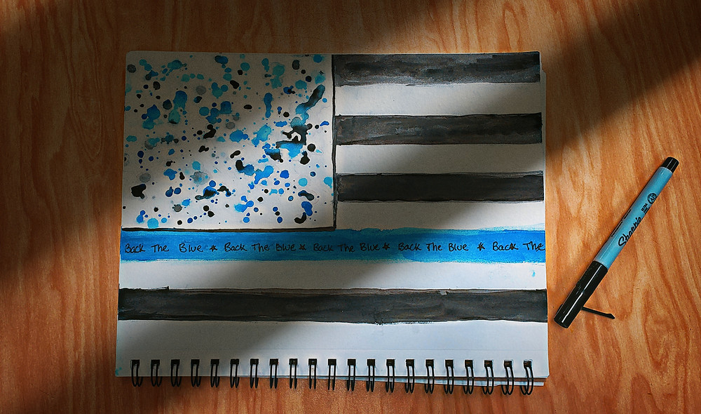 """""""Back the Blue"""" artwork on table by Gabriella Angelucci, Eastern Christian"""