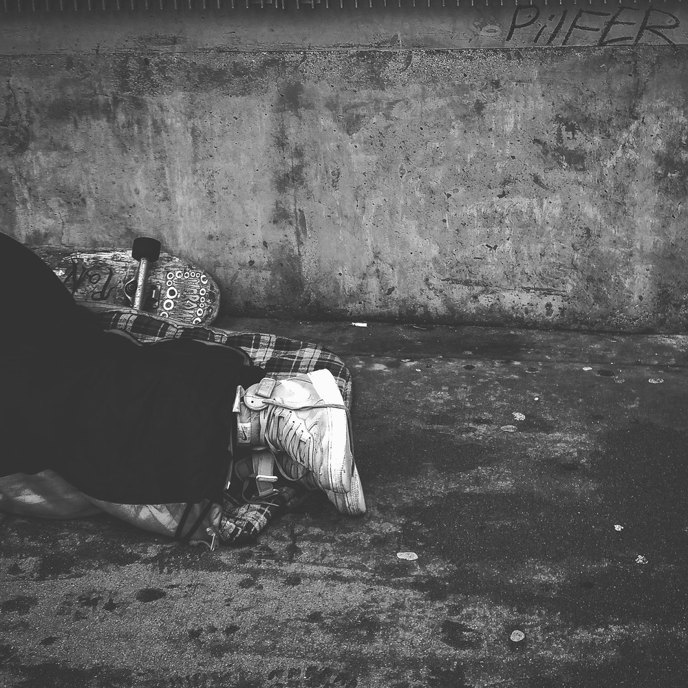 A homeless man with sneakers laying down on the side of the road