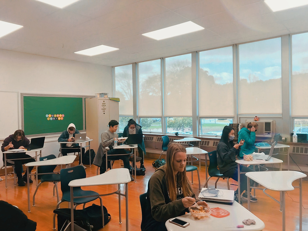 Students sit at desks eating during inside lunch block 2